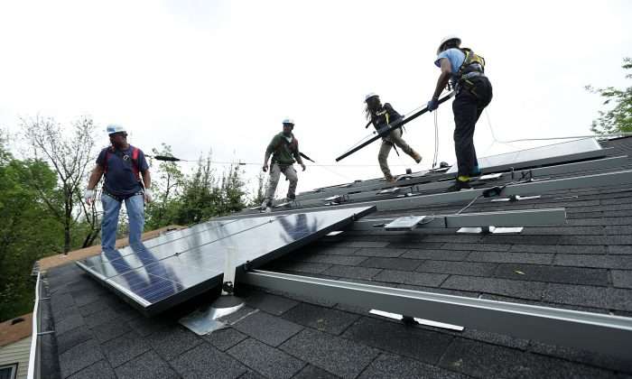 Workers put solar panels down during an installation in Washington on May 3. (Alex Wong/Getty Images)