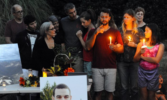 Sam Harris, center, older brother of Daniel Harris signs to the crowd during a candlelight vigil along Seven Oaks Drive to remember Daniel Harris, Monday, Aug. 22, 2016 in Charlotte, N.C. Daniel Harris, a deaf man who was shot and killed by a North Carolina state trooper after he didn't stop for the officer's blue lights was unarmed and likely did not understand the officer's commands, the slain man's family says.  (David T. Foster III/The Charlotte Observer via AP)