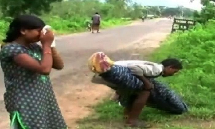 Dana Manjhi and is 12-year-old daughter are seen as he lifts the body of his wife (YouTube/screenshot)