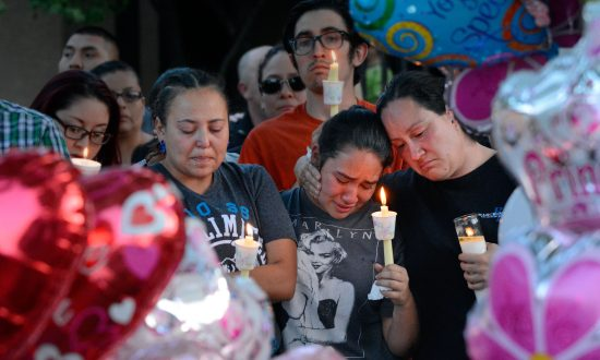 (L-R) Nicole Maldonado, Myriah Flores, and her mother Sharlene Benavidez attend a candlelight vigil for 10-year-old Victoria Martens at the apartment complex in Albuquerque, N.M., on Aug. 25, 2016, where the young girl lived and was killed. (Jim Thompson/The Albuquerque Journal via AP)