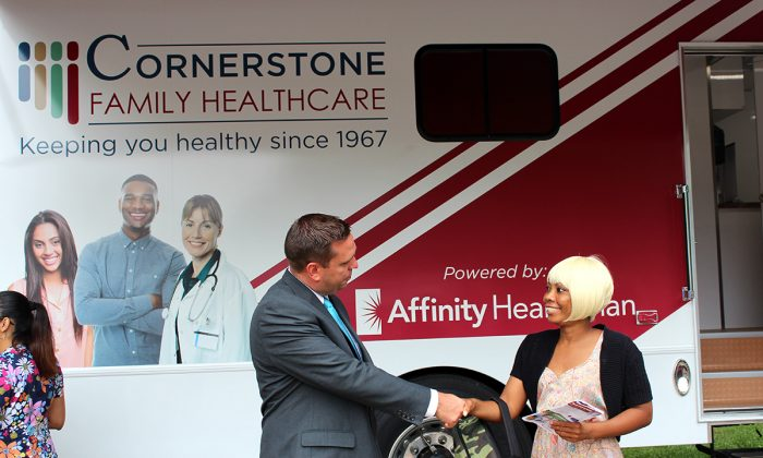 County Executive Steve Neuhaus (L) shakes hands with HONOR housing resident Labriska Brown in front of new mobile health van in Middletown on Aug. 17, 2016. (courtesy of office of County Executive)