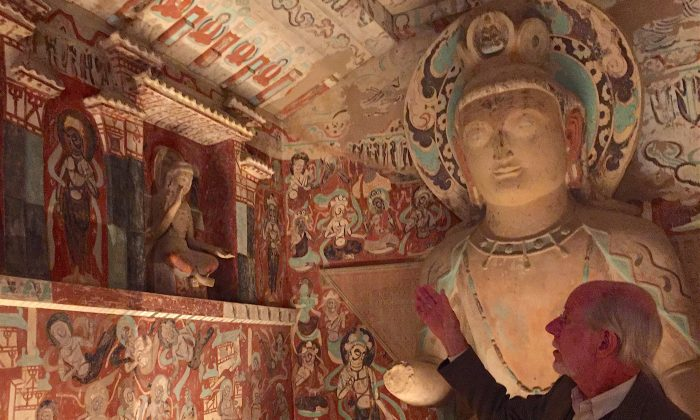 Neville Agnew, a senior principal project specialist at the Getty Conservation Institute, describes the meaning of wall paintings in a replica of a cave from Dunhuang, China at the Getty Center museum in Los Angeles, Calif. on June 1, 2016. (Sarah Le/Epoch Times)