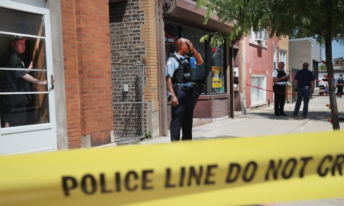 Police investigate a crime scene after two people were shot in Chicago on June 15. (Scott Olson/Getty Images)