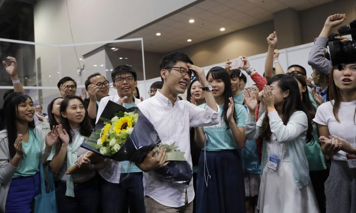 Political party Demosisto's Nathan Law, center, who helped lead the 2014 protests, celebrates with his supporters after winning a seat at the legislative council elections in Hong Kong, Monday, Sept. 5, 2016. A new wave of anti-China activists appeared headed for victory in Hong Kong's most pivotal elections since the handover from Britain in 1997, which could set the stage for a fresh round of political confrontations over Beijing's control of the city. (AP Photo/Kin Cheung)