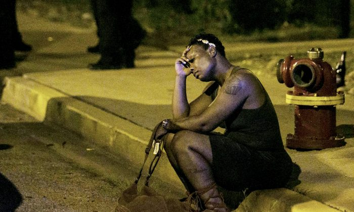 In this Aug. 7, 2016, photo, a woman sits on the curb as police in the background investigate the scene where gunfire at a birthday party left a man dead and a woman injured.  (Ashlee Rezin /Chicago Sun-Times via AP)