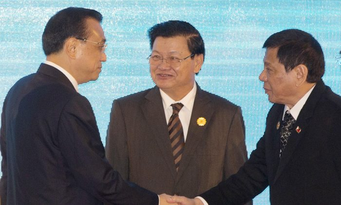 Chinese Premier Li Keqiang, left, shakes hands with Philippine's President Rodrigo Duterte, right, as Laos' Prime Minister Thongloun Sisoulith, watches during the 19th ASEAN-China summit, in Vientiane, Laos, Wednesday, Sept. 7, 2016. (AP Photo/Gemunu Amarasinghe)