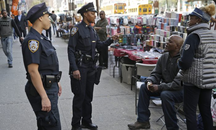 Police officers Lanora Moore, left, and Shakara President talk with a vendor on 125th Street in the Harlem section of New York, Wednesday, April 29, 2015. (AP Photo/Seth Wenig)