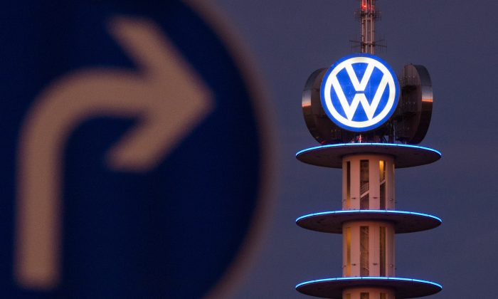 A street sign in front of an illuminated logo of German automaker Volkswagen in Hanover, Germany. (Julian Stratenschulte/AFP/Getty Images)