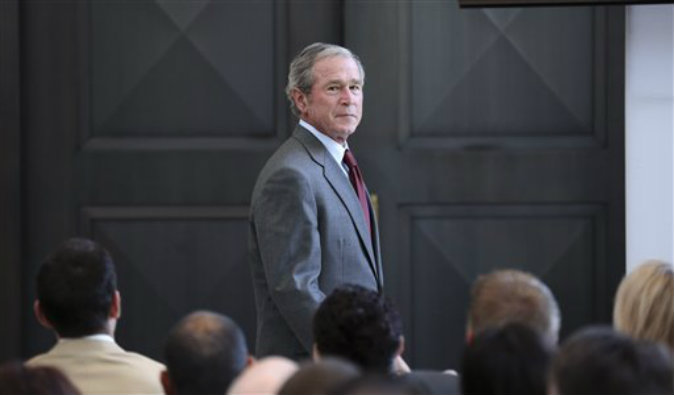 Former President George W. Bush walks off the stage after giving a speech before a U.S. citizen swearing in ceremony at the The George W. Bush Presidential Center in Dallas on July 10, 2013. (AP Photo/LM Otero)