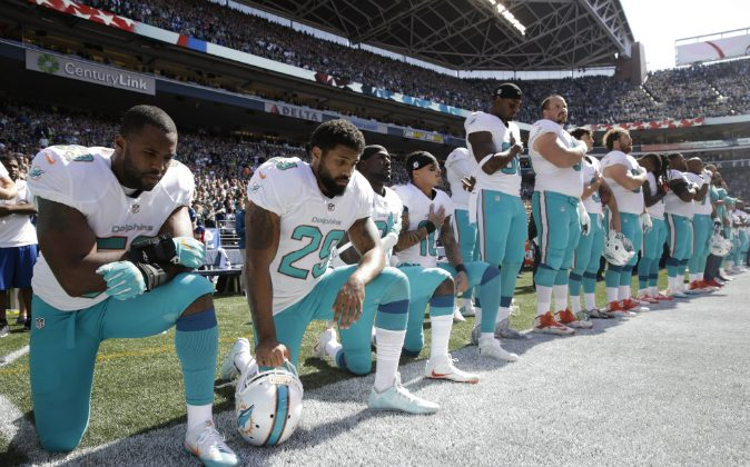 (L-R) Miami Dolphins' Jelani Jenkins, Arian Foster, Michael Thomas, and Kenny Stills, kneel during the singing of the national anthem before an NFL football game against the Seattle Seahawks, Sunday, Sept. 11, 2016, in Seattle. (AP Photo/Stephen Brashear)