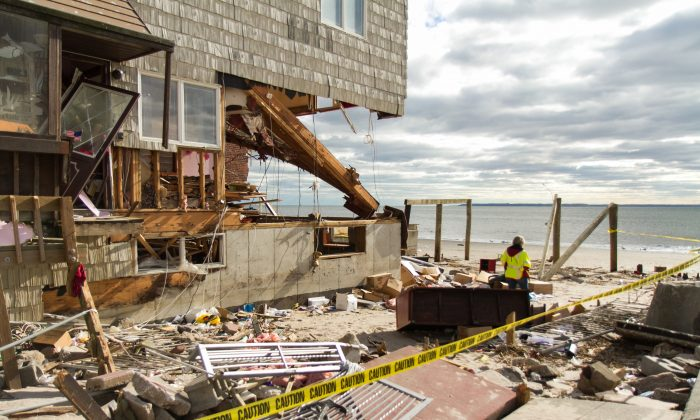 A worker surveys the area of a house that was destroyed by Hurricane Sandy at Sea Gate Beach in Brooklyn on Nov. 6, 2012. (Kristen Meiwether for Epoch Times)