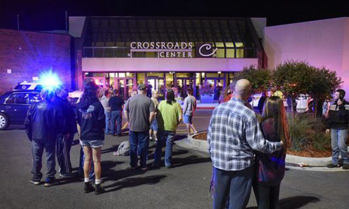 People stand near the entrance on the north side of Crossroads Center mall between Macy's and Target as officials investigate a reported multiple stabbing incident in St. Cloud, Minn., on Sept. 17, 2016. (Dave Schwarz/St. Cloud Times via AP)