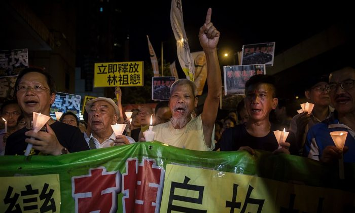 Protesters attend a candlelight vigil in support of China's Wukan village outside the Chinese Liason Office in Hong Kong on Sept. 17, 2017. (Isaac Lawrence/AFP/Getty Images)