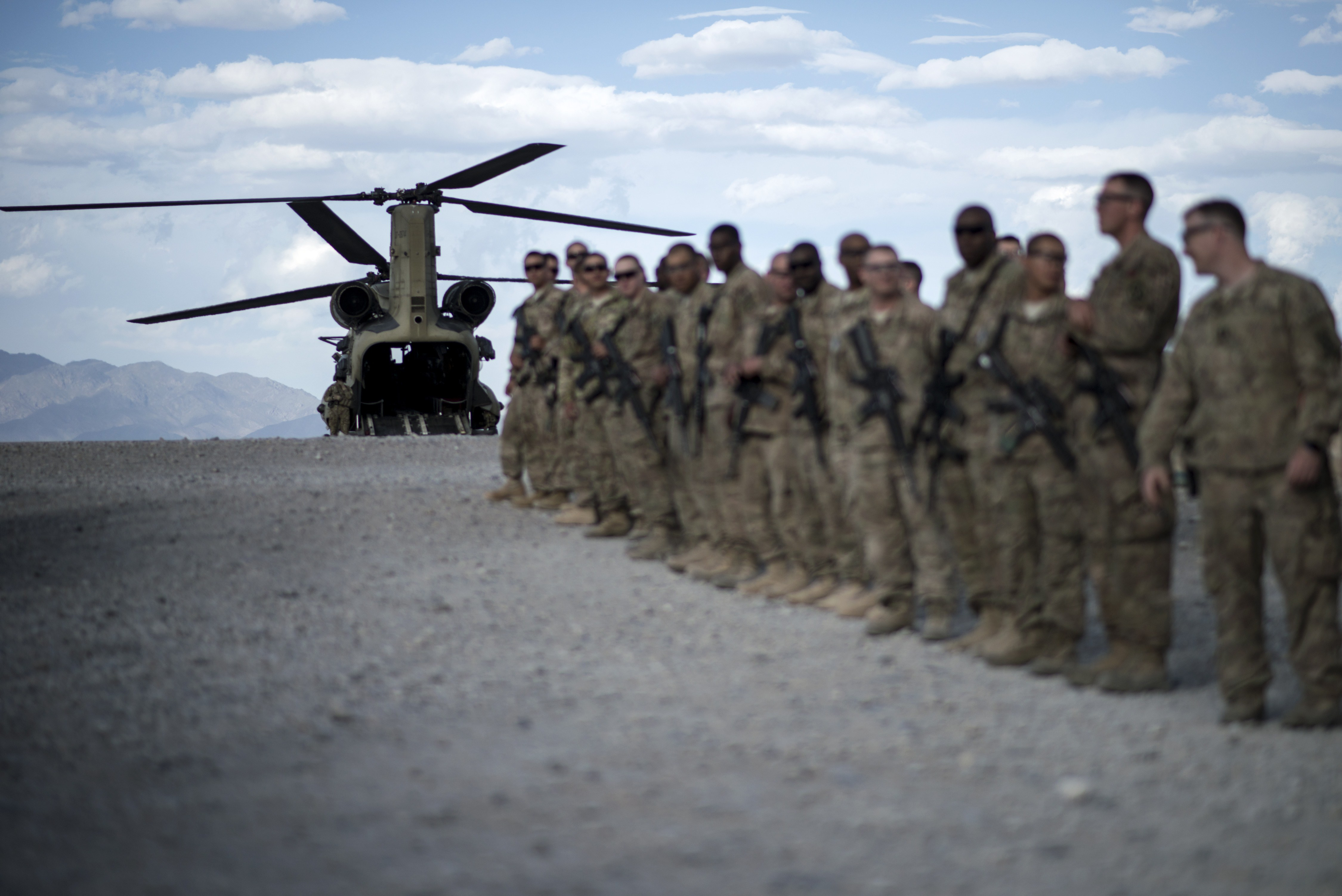 """U.S. soldiers lining up as they wait to bid farewell to wounded veterans during """"Operation Proper Exit"""" at Forward Operating Base Shank in Afghanistan's Logar Province on on May 28, 2014. (Brendan Smialowski/AFP/Getty Images)"""