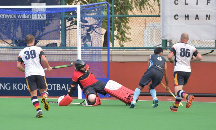 HKFC-A player (No 8) pushes the ball behind the HKCC-A goalie for his team mate to slide the ball into the goal for HKFC's 1st of 2 goals in this exciting premier Hockey match at HKFC on Sunday Sept 18, 2016. HKFC-A won the match 2-0. (Bill Cox/Epoch Times)