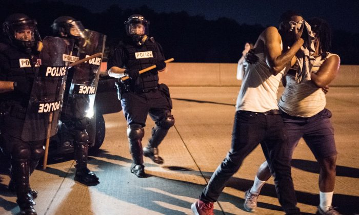 A protester reacts to a sprayed deterrent while blocking traffic on the I-85 (Interstate 85) during protests in the early hours of September 21, 2016 in Charlotte, North Carolina. (Sean Rayford/Getty Images)