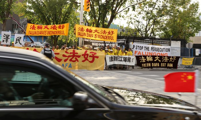 Falun Gong practitioners hold banners in downtown Ottawa as  Chinese Premier Li Keqiang's motorcade passes by on Sept. 22, 2016. (Donna He/Epoch Times)