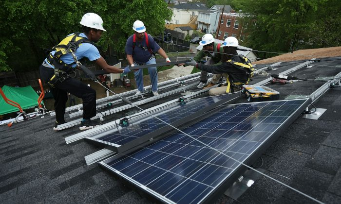 Workers install solar panels on a home in Washington on May 3. (Alex Wong/Getty Images)