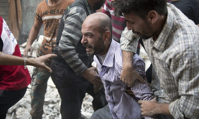 A grief-striken Syrian man is comforted by people as rescuers pull the body of his daughter from the rubble of a budling following government forces air strikes  in Aleppo on Sept. 27, 2016. (KARAM AL-MASRI/AFP/Getty Images)