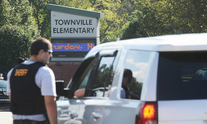 Members of law enforcement talk in front of Townville Elementary School on Wednesday, Sept. 28, 2016, in Townville, S.C.   A teenager opened fire at the South Carolina elementary school Wednesday, wounding two students and a teacher before the suspect was taken into custody, authorities said.  (AP Photo/Rainier Ehrhardt)