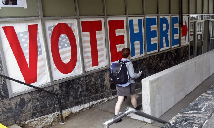 A voter woman passes a large sign before voting in Minneapolis on Sept. 23, 2016. (AP Photo/Jim Mone)
