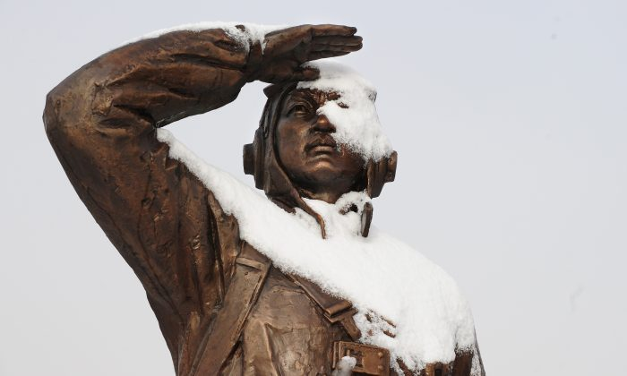 """A monument dedicated to a Chinese war veteran looking towards North Korea the banks of the Yalu River in Dandong is patially covered in snow on November 27, 2010 in northeast China's Liaoning province, across from North Korean border town of Siniuju which is connected by the Sino-Korean Friendship Bridge after a night of snowfall. The United States has sought to reassure China over joint US-South Korean military exercises, with the Pentagon insisting the war games were """"not directed"""" at Beijing with the four-day exercises starting November 28 coming in the wake of North Korea's artillery bombardment of a South Korean island.  AFP PHOTO / Frederic J. BROWN (Photo credit should read FREDERIC J. BROWN/AFP/Getty Images)"""