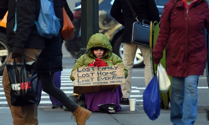A homeless woman on 5th Avenue tries to stay warm in the cold temperatures last January in New York.  (TIMOTHY A. CLARY/AFP/Getty Images)