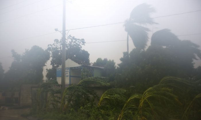A house with its roof torn off by the winds caused by Hurricane Matthew stands in Leogane, Haiti. Tuesday, Oct. 4, 2016. Matthew slammed into Haiti's southwestern tip with howling, 145 mph winds tearing off roofs in the poor and largely rural area, uprooting trees and leaving rivers bloated and choked with debris. (AP Photo/Dieu Nalio Chery)