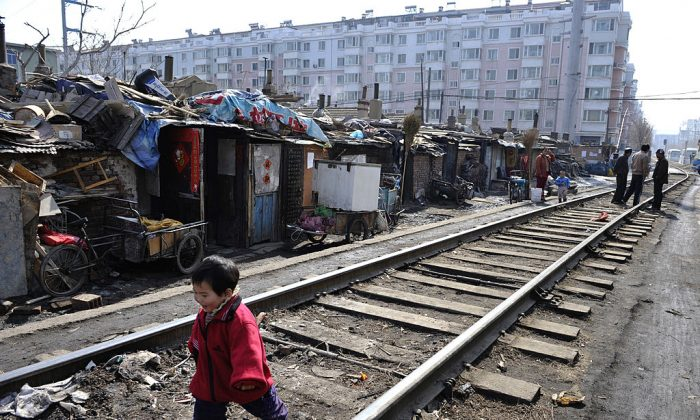 A child plays along a railway at a shanty town where residents will move into low-rent apartments provided by the government in Shenyang of Liaoning Province on March 11, 2009. (China Photos/Getty Images)