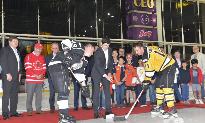 Puck-drop by Stefan Pouliot of main Sponsor Quam Financial Services under the watchful eye of CIHL Officials, Jeff Nankivell, Canada Consul General for Hong Kong and Macau, (wearing Canada Jersey) and other guests to start the 2016-17 season for the Hong Kong CIHL league at Mega Ice on Thursday Oct 6, 2016. (Bill Cox/Epoch Times)