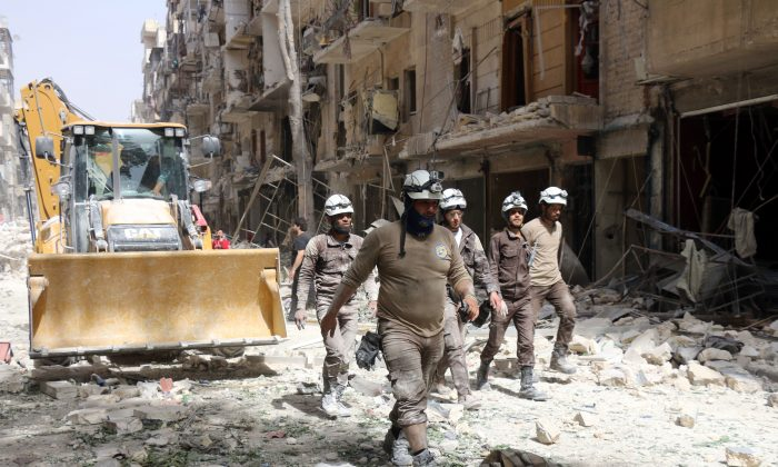 Syrian Civil Defense volunteers, known as the White Helmets, walk amidst the debris following a reported airstrike by Syrian government forces in the rebel-held neighborhood of Sukkari in the northern city of Aleppo on June 3, 2016. (Thaer Mohammed/AFP/Getty Images)