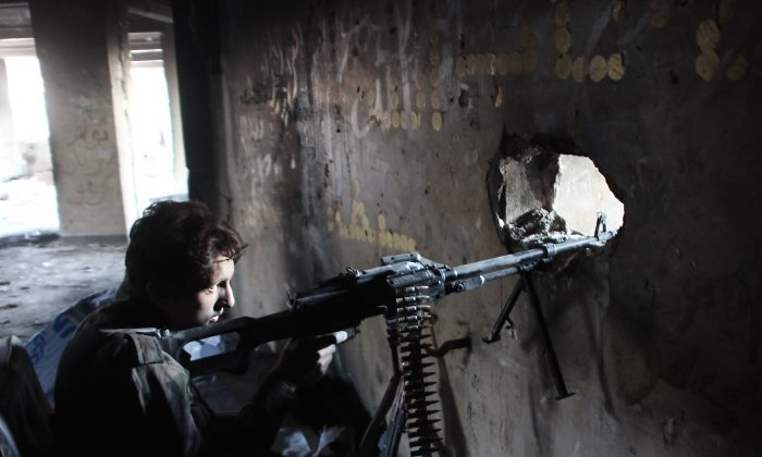 A member of Syria's pro-government forces guards a look out point as they advance on Aleppo's rebel-held Bustan al-Basha neighborhood on Oct. 6, 2016. (George Ourfalian/AFP/Getty Images)