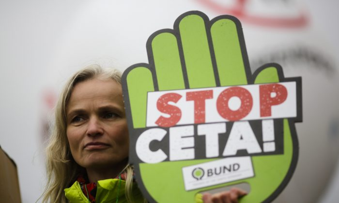 A demonstrator during an anti-CETA protest in front of the chancellery in Berlin on Oct. 12, 2016. Opposition to the Comprehensive Economic and Trade Agreement is festering among Belgium's French-speaking Walloons, which could pose a problem for completion of the deal. (AP Photo/Markus Schreiber)
