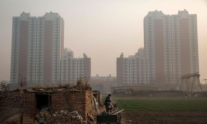 An elderly Chinese farmer stands outside her home on farmland backdropped by a new housing development outside Beijing on Nov. 21, 2014. (Kevin Frayer/Getty Images)