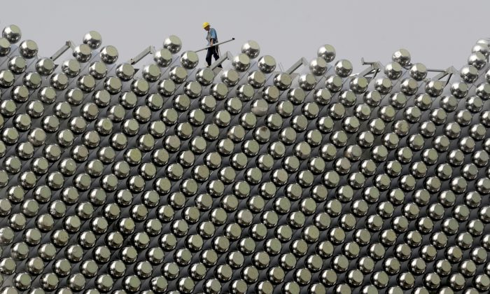A laborer works on the rooftop of the Wanda Reign Wuhan Hotel, in Wuhan, central China's Hubei Province, on Aug. 27, 2013. (STR/AFP/Getty Images)