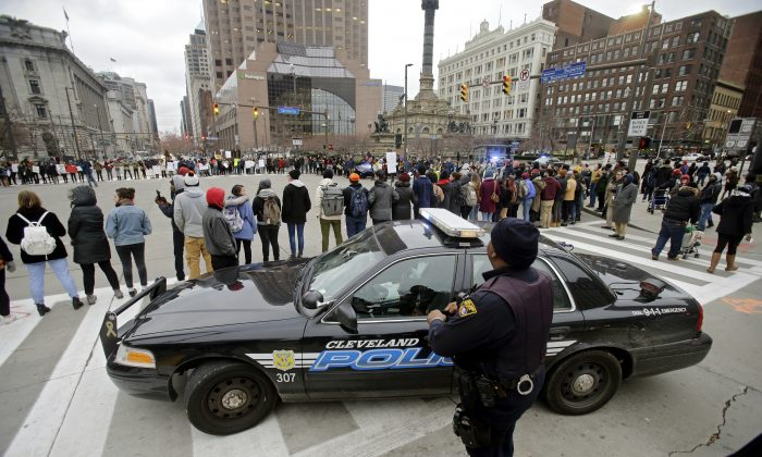 Cleveland police watch demonstrators block Public Square iduring a protest over the police shooting of 12-year-old Tamir Rice on Nov. 25, 2014. (AP Photo/Mark Duncan, File)