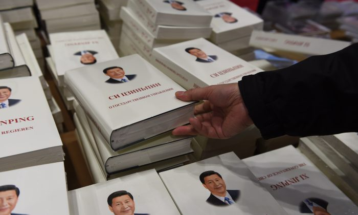 A staff member arranges books about Chinese President Xi Jinping in the media center for the Asia-Pacific Economic Cooperation (APEC) summit in Beijing on November 5, 2014. (Greg Baker/AFP/Getty Images)