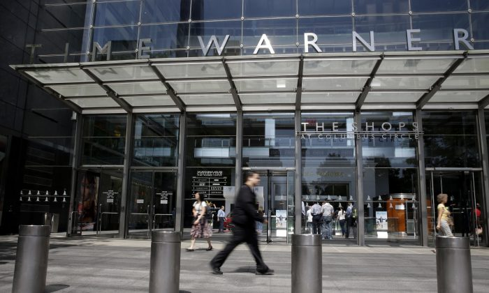 Pedestrians walk by an entrance to the Time Warner Center in New York on May 26, 2015. AT&T announced on Sept. 22 the acquisition of Time Warner for $85 billion in a stock-and-cash deal. (AP Photo/Mary Altaffer)