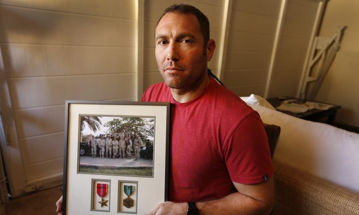 Robert D'Andrea, a retired Army major and Iraq war veteran, holds a frame with a photo of his team on his first deployment to Iraq on Oct. 21, 2016. (Al Seib/Los Angeles Times via AP)