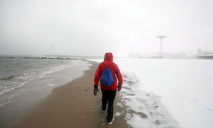 A man walks on the Coney Island beach during a morning snow storm in the Brooklyn borough of New York City on Feb. 22, 2008. (Mario Tama/Getty Images)