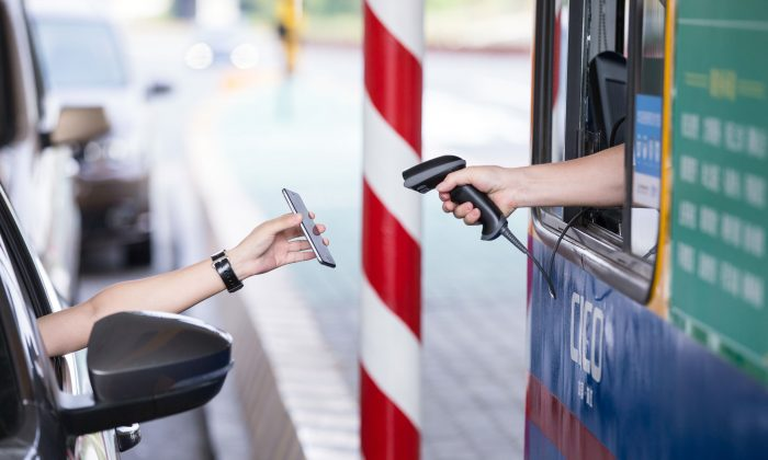 A driver uses Alipay on his smartphone to pay a highway toll, on the Hangzhou-Ningbo Expressway in Hangzhou, Zhejiang province Sept. 21. (STR/AFP/Getty Images)
