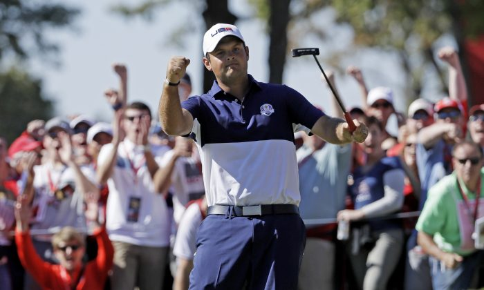 Patrick Reed reacts after winning the fifth hole during a singles match at the Ryder Cup golf tournament, at Hazeltine National Golf Club in Chaska, Minn. (AP Photo/David J. Phillip)