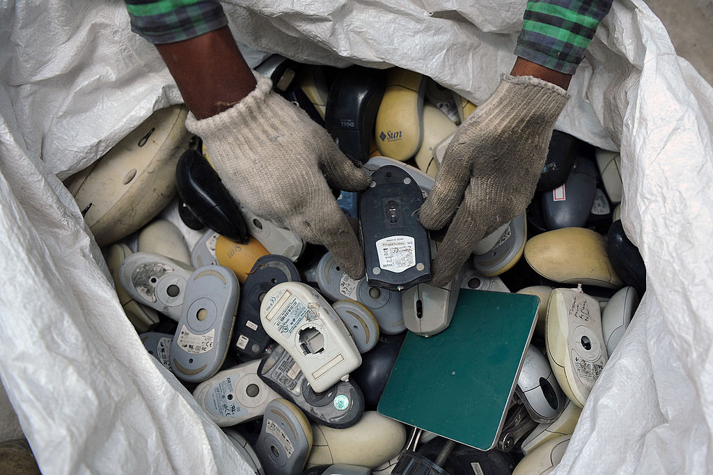 An Indian worker sifts through a bag full of defunct computer mice prior to disassembly at Ash Recyclers, an e-waste management firm in Bangalore on June 5, 2013. (Manjunath Kiran/AFP/Getty Images)