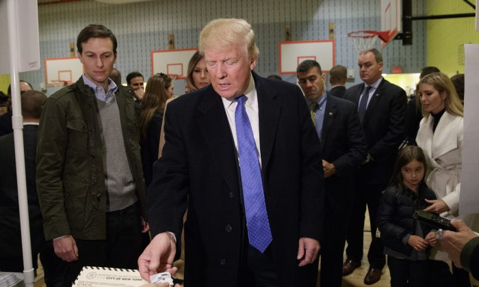 Republican presidential candidate Donald Trump is handed a sticker before casting his ballot at PS-59,  in New York on Nov. 8, 2016. (AP Photo/ Evan Vucci)