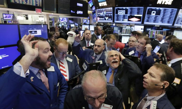 Specialist Charles Boeddinghaus (L) directs trading at his post on the floor of the New York Stock Exchange, on Nov. 9, 2016. (AP Photo/Richard Drew)