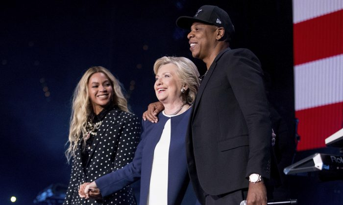 FILE - In this Nov. 4, 2016 file photo, Democratic presidential candidate Hillary Clinton, center, appears on stage with artists Jay Z, right, and Beyonce during a free concert at at the Wolstein Center in Cleveland. Few presidential candidates attracted so much celebrity support as did the former first lady and Secretary of State, but to so little reward. Rallies in Ohio with Beyonce and Jay Z did not prevent Republican rival and President-elect Donald Trump from prevailing. (AP Photo/Andrew Harnik, File)
