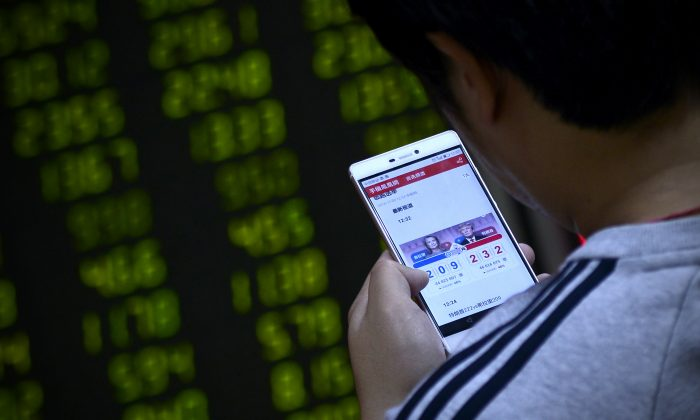 A Chinese investor watches the U.S. presidential election on his smartphone at a securities company in Beijing on Nov. 9. (WANG ZHAO/AFP/Getty Images)