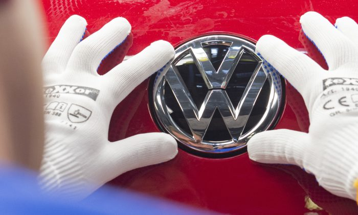 A worker checks the Volkswagen sign on a Golf car, in this file photo. (AP Photo/Jens Meyer, file)