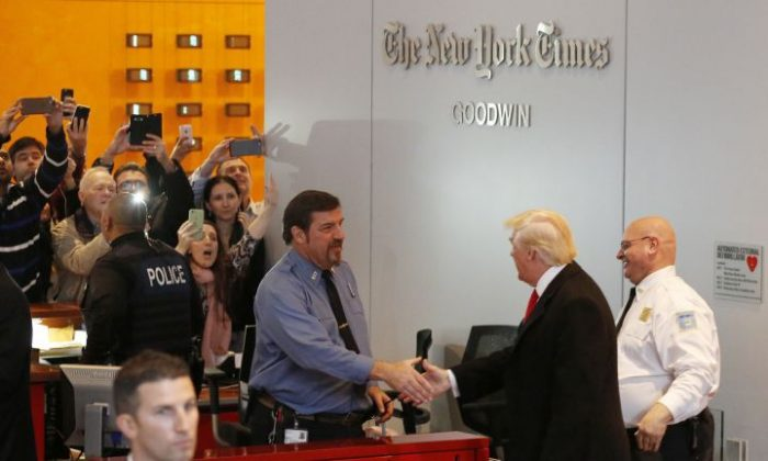 Onlookers watch as President-elect Donald Trump shakes hands with a security guard as he leaves the New York Times building following a meeting, Tuesday, Nov. 22, 2016, in New York.  (AP Photo/Mark Lennihan)