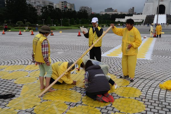 Falun Gong practitioners help out with the character formation preparation in Taipei on Nov. 24, 2016, two days before the actual formation. (Frank Fang/Epoch Times)